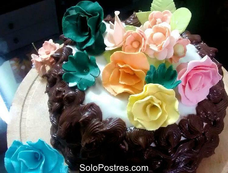 Torta de cumpleaño decorada con ganache y rosas de varios colores